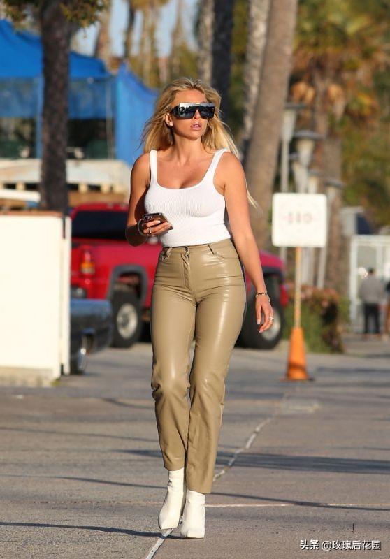 克洛伊·特拉穿着军绿色皮革长裤和白色背心高挑有型