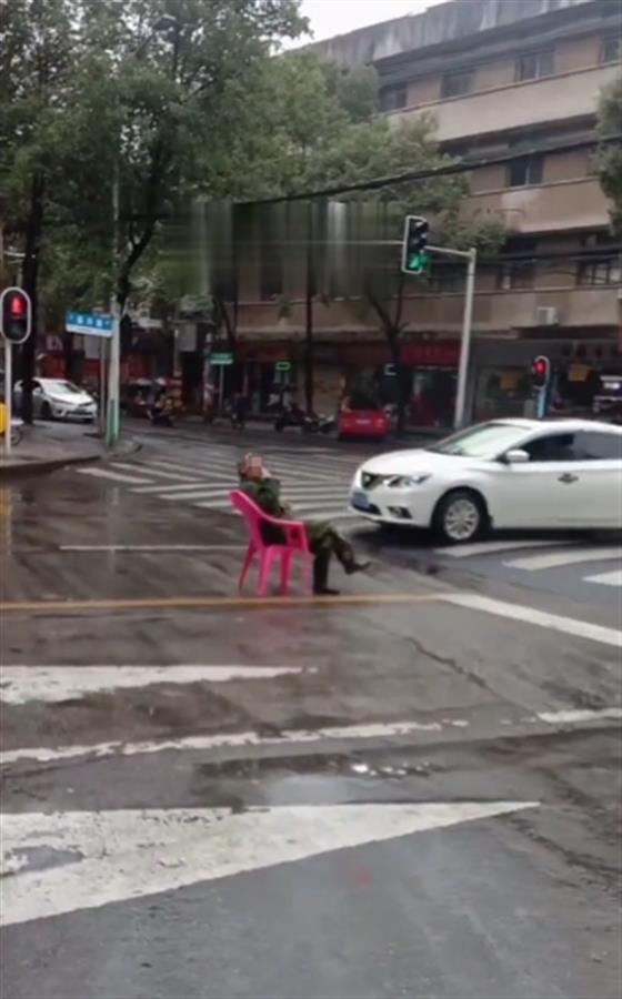 湖南一老人搬凳子坐路中间,目击者:可能喝了酒,被警方带走